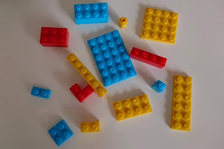 Various sized pieces of Brix Play in blue, red and yellow colours scattered over a white table