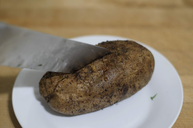A knife cutting a slit in the top of the potato.