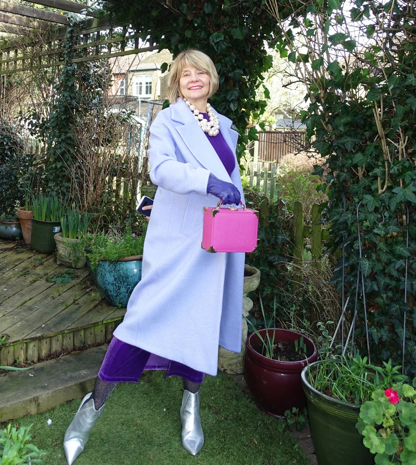 A lilac cocoon coat is warm and stylish over purple with silver accessories, as shown by over-50s style blog Is This Mutton