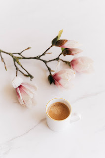flowers on a branch with cup of coffee in white mug