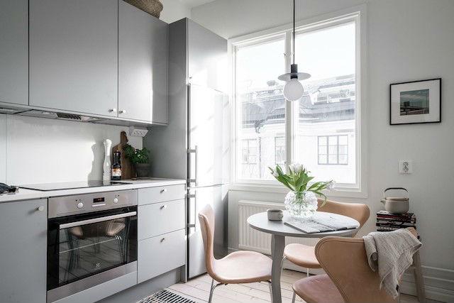 Cocina sencilla con mobiliario en gris y suelo de madera natural. Con pequeño office.