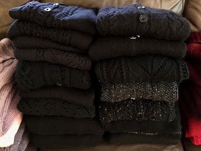 Two stacks of hand-knitted sweaters in black