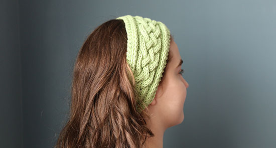 Girl turned away from camera in front of a blue background, wearing a light green hand-knit cabled headband.