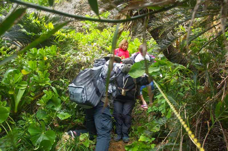 people assist in steep descent towards cave