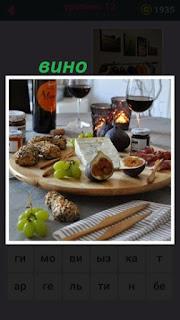 на столе лежит закуска разного рода и стоит бутылка вина с фужерами