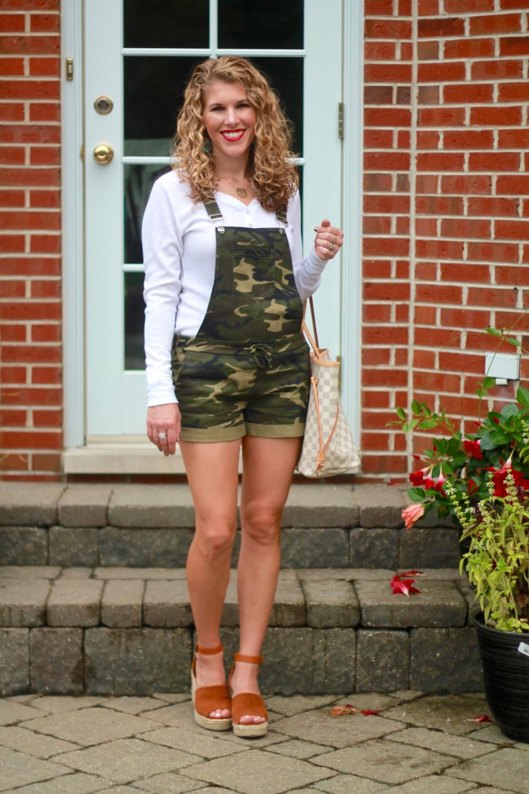 camo shorts overalls, white long sleeve henley, LV azure Neverfull, cognac suede wedges