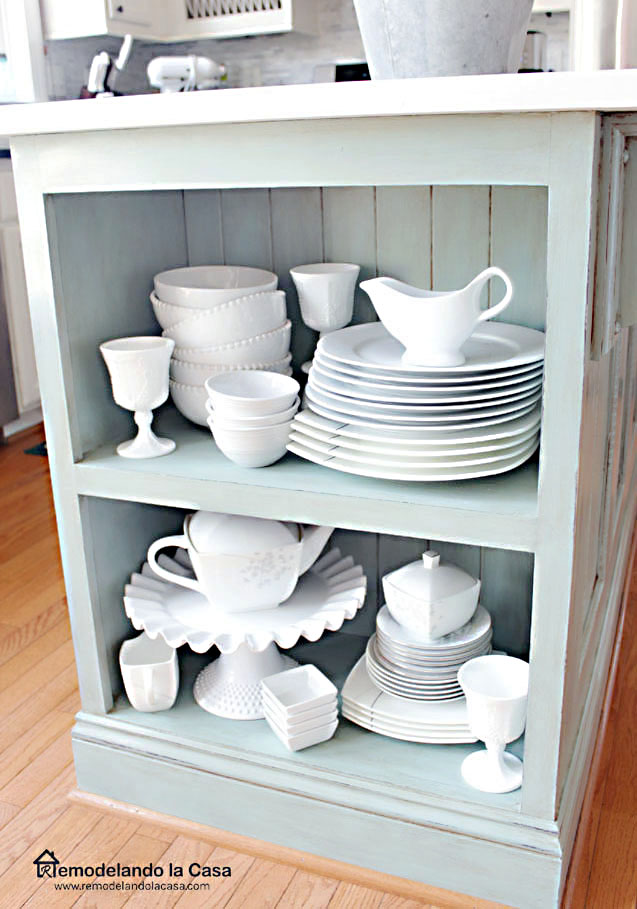 Kitchen island with shelves on side and white dinnerware