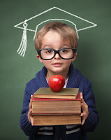 adorable boy holding stack of books with an apple leaning back against chalkboard with a grad cap drawing