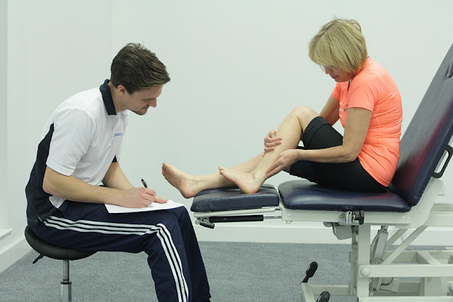 Professional assessing gastrocnemius and soleus for treatment.