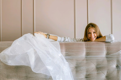 A woman smiling behind a headboard wrapped in foil.
