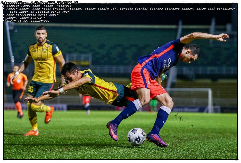 ALOR SETAR 04 MAY 2021. Kedah player, Mohd Rizal Ghazali (center) is pushed by JDT player, Gonzalo Gabriel Cabrera Giordano (right) in the Super League 2021 match at the Darul Aman Stadium. STR/LUQMAN HAKIM ZUBIR