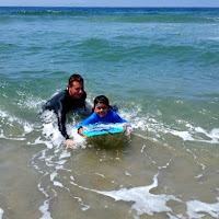 Camp Counselor Jeremy Polon teaches camper Uriel how to boogie board at beach camp