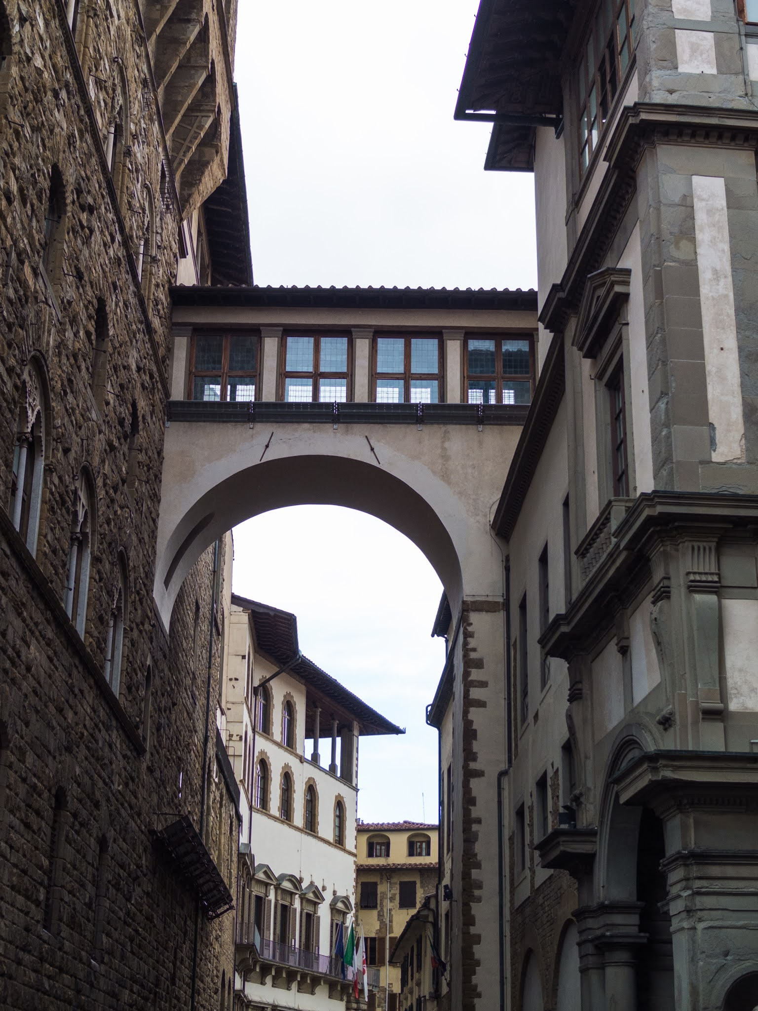 View of a tall archway connecting two buildings in Florence.