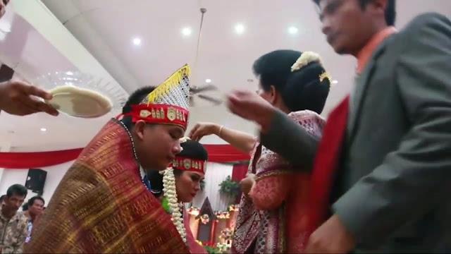 (25/12/19)Ulos Hela Pada Pernikahan Adat Batak  Ulos adalah Kain tenun khas Batak Yang Memiliki beragam motif. dari segi tampilanya yang di bentuk berupa selendang,maupun baju(rompi).    Kata 'Ulos' adalah bahasa batak yang jika di artikan kedalam bahasa nasional indonesia adalah 'selimut'.Namun Ulos dari tenunan khas Batak ini bukanlah Seperti selimut yang di pakai pada umumnya oleh manusia.benda sakral ini  memiliki sejarah perjalanan yang panjang dari sejak adanya suku Batak.    HORAS..kali ini kita akan membahas acara adat Batak Toba yaitu proses berjalanya Ulos Hela Pada Acara Pernikahan Suku Batak    Horas...kali ini kita akan membahas acara adat Batak Toba yaitu proses berjalanya Ulos Hela.   Ulos Hela Pada Acara Pernikahan Adat Batak Toba  Hal paling menyentuh dalam menyaksikan acara adat Batak Toba yaitu pada saat detik-detik penyerahan ulos Hela.dimana disini banyak pesan maupun nasehat yang sangat berharga dari kedua orangtua pengantin tersebut.  Ulos Hela Pada Acara Pernikahan Adat Batak Toba      Jika kamu menyaksikan cuplikan video di atas tentu rasa bahagia,haru,sepi bercampur bahagia pasti ada.  Tidak jarang rasa haru,sedih bercampur bahagia dalam menyaksikannya.selain itu bagi kamu kaum suku Batak Toba yang ingin belajar menjadi Raja parhata,atau Raja adat,sangat di sarankan untuk menyaksikan proses awal berjalanya acara pernikahan,acara kematian,martumpol,dan lain lain,untuk memahami hal-hal apa saja yang di lakukan maupun di ucapkan dalam detik-detik acara yang sedang berlangsung.  Baca Juga: Partuturan Pada Suku Batak Toba Macam-macam Seni Budaya Batak Cerita Lengkap Sejarah Asal Usul Suku Batak Ciri Khas,Macam dan Adat Istiadat Suku Batak Yang Harus kamu Ketahui Kumpulan Umpasa Batak Tapsel,Angkola/Mandailing Arti dan Makna Di Balik Kata Horas Pada Suku Batak Toba Kumpulan dan Macam-macam Umpasa Budaya Batak Toba Salam Khas Dari Berbagai Jenis Suku Batak Kumpulan Pantun Umpasa Batak Lucu Dan Gokil Pengertian Filosofi Hamoraon,Hasangapon,Hagabeon