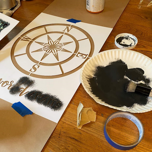 Photo of a compass stencil being stenciled onto brown paper