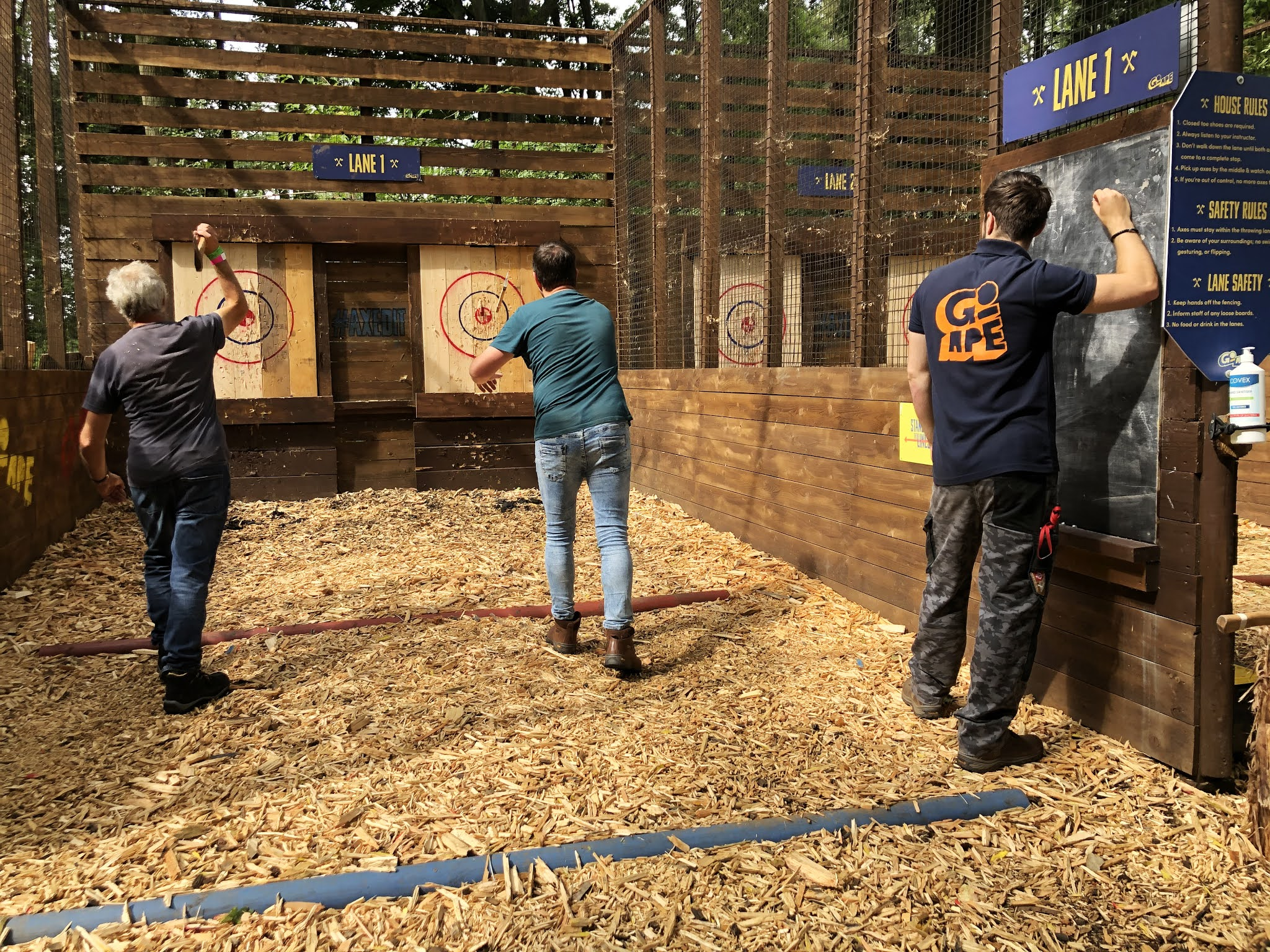 Two men throwing axes towards a wooden target board while another man standing to the side is keeping score