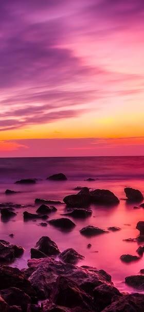 خلفية غروب الشمس على شاطئ الأحجار المبعثرة