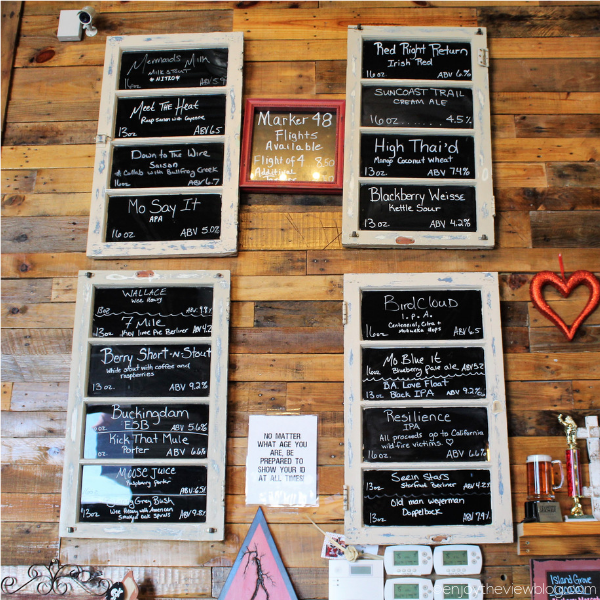 chalk boards on a wall with lists of craft beer