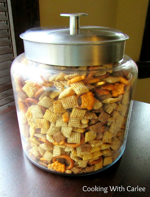 big glass cookie jar filled with chex mix