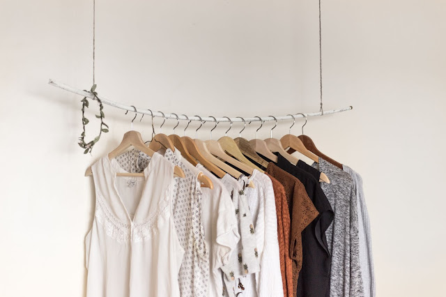 The image shows a clothing rail which is held up by twine. On the rail is a collection of women's clothing. The clothing is ethically sourced