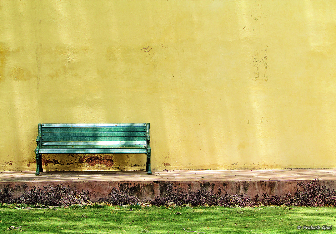 A Minimalist Photo of a Green bench against a yellow wall at Jantar Mantar, Jaipur.