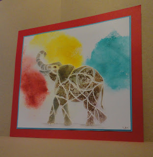 Gilded elephant image over bursts of red, yellow, blue, mounted on blue and red