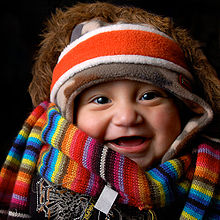 A baby wearing many items of winter clothing: headband, cap, fur-lined coat, shawl and sweater
