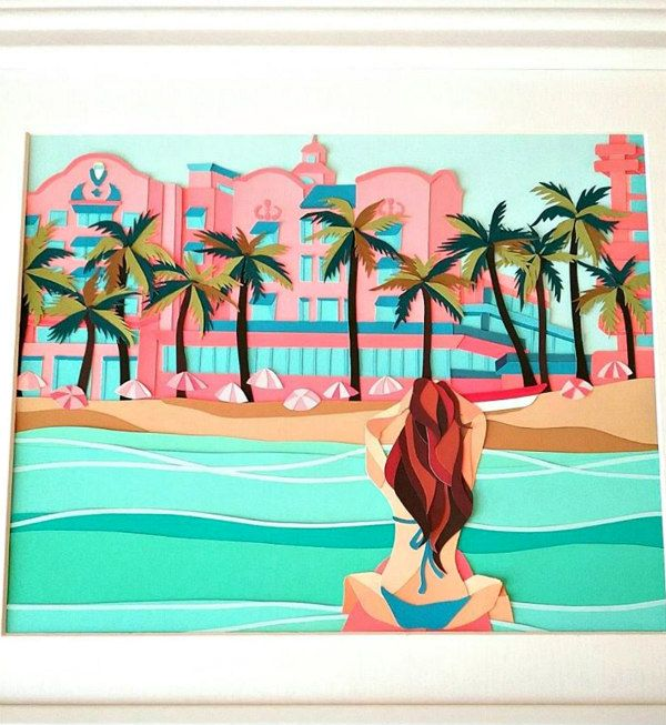 paper cut scene of a young woman sitting on a surfboard in the ocean in front of Royal Hawaiian hotel