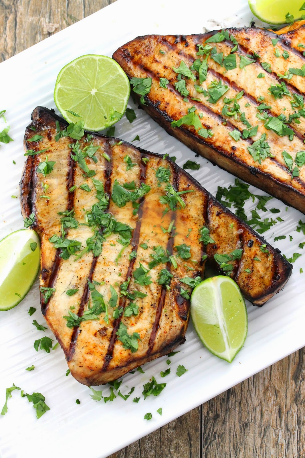Grilled swordfish with cilantro on top and lime wedges