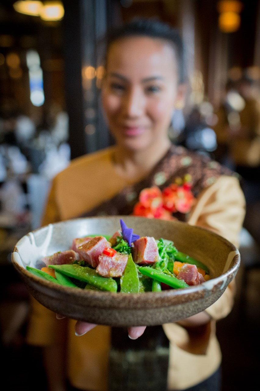close up photo of a woman holding a bowl of food made in Chaophraya.