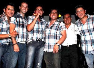 Foto de la Orquesta Candela con camisa a cuadro y jean