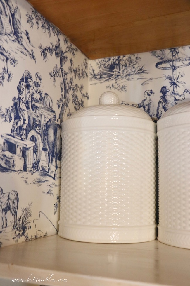 French Country Pantry Makeover with white basket weave canisters and Seasons Toile Wallpaper