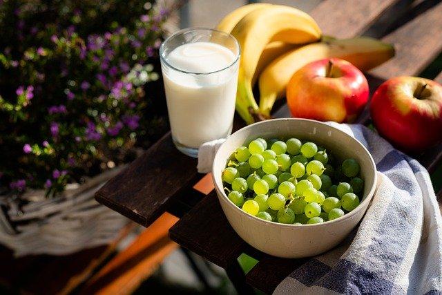 Mesa con Plato de Fruta y un vaso de vidrio con leche para Dieta
