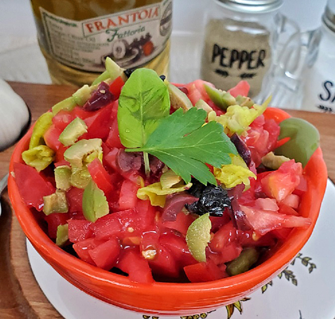 this is a bowl of chopped tomatoes, olives, peppers and Italian herbs to make a salsa