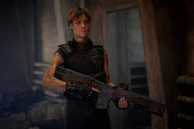 Movie scene from Terminator Dark Fate where Mackenzie Davis prepared for battle with a machine gun