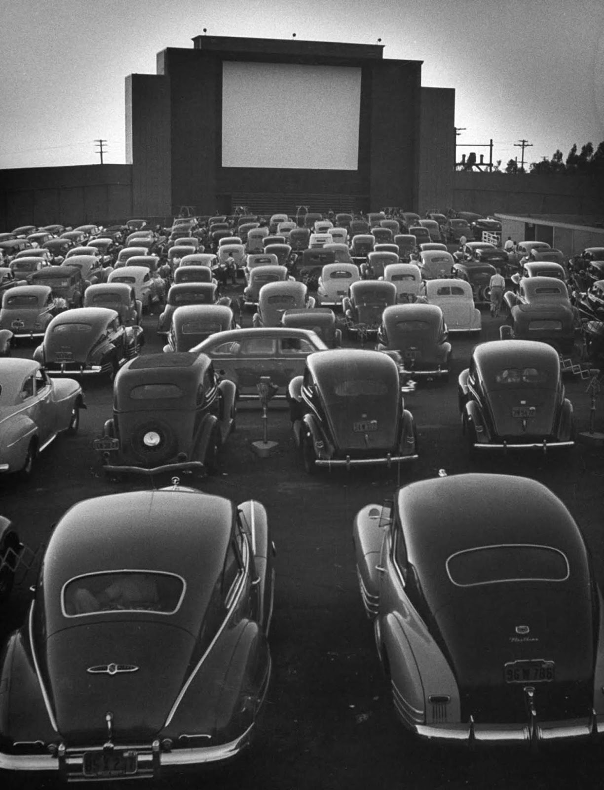 Cars filling lot at new Rancho Drive-In Theater at dusk before the start of the feature movie.