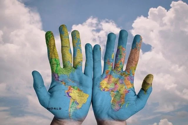 Globalization - world map depicted on hands - evolution, causes and consequences