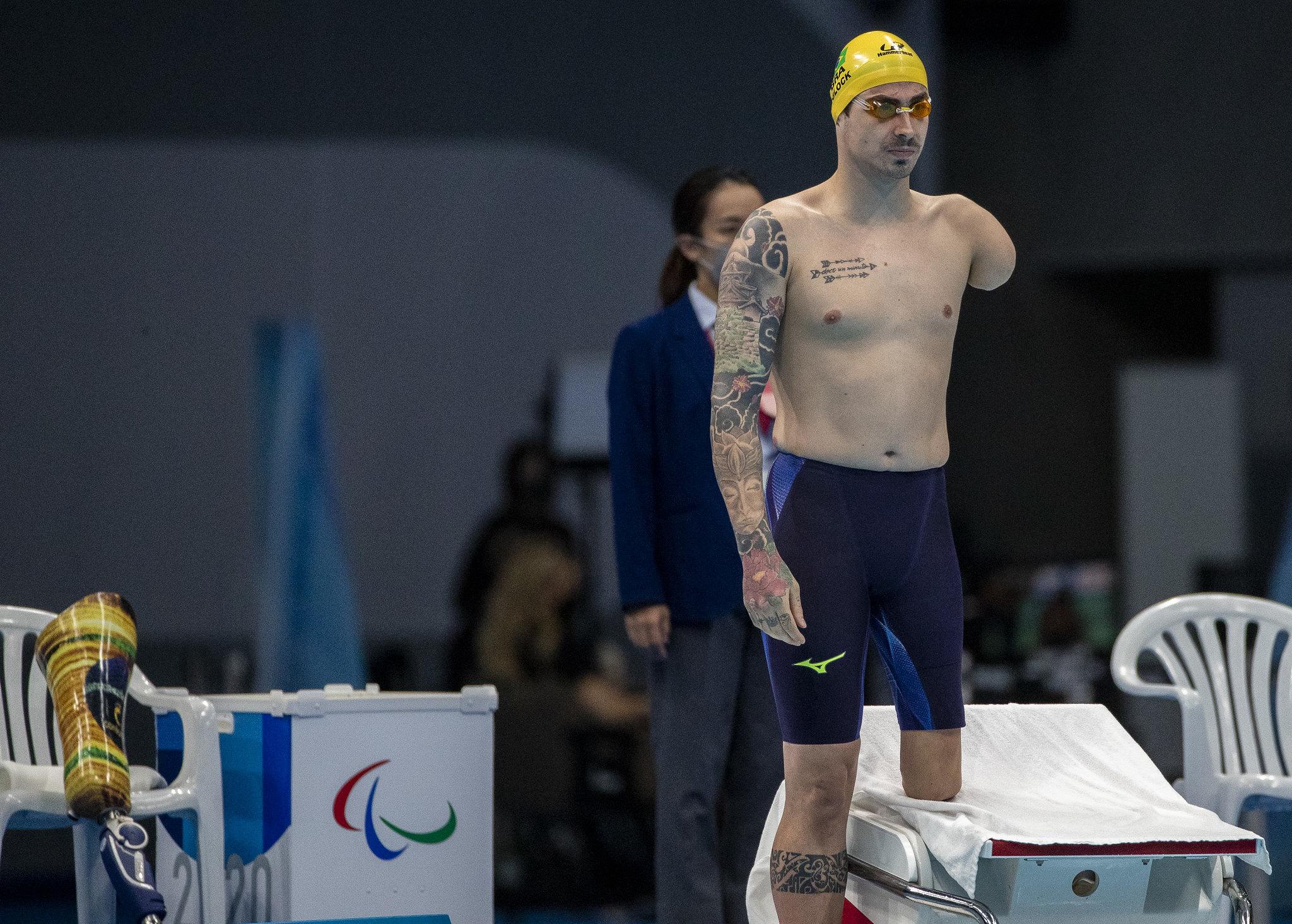 Talisson Glock, sem braço e parte da perna do lado esquerdo, a beira da piscina em pé.
