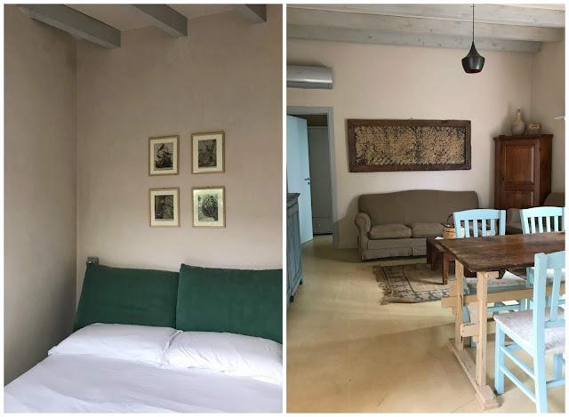 A la izquierda detalle del cabecero de otro dormitorio con cuadros en la pared. A la derecha vista del salón comedor con sofá marrón, mesa de madera y sillas azules