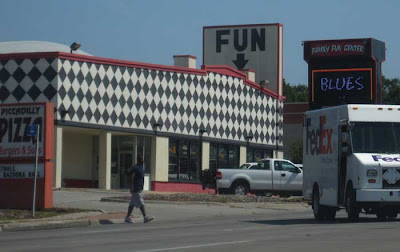 Black and white harlequin checked building with sign above saying just FUN with an arrow pointing downward