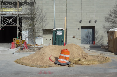 Pile of dirt and Texas Outhouse