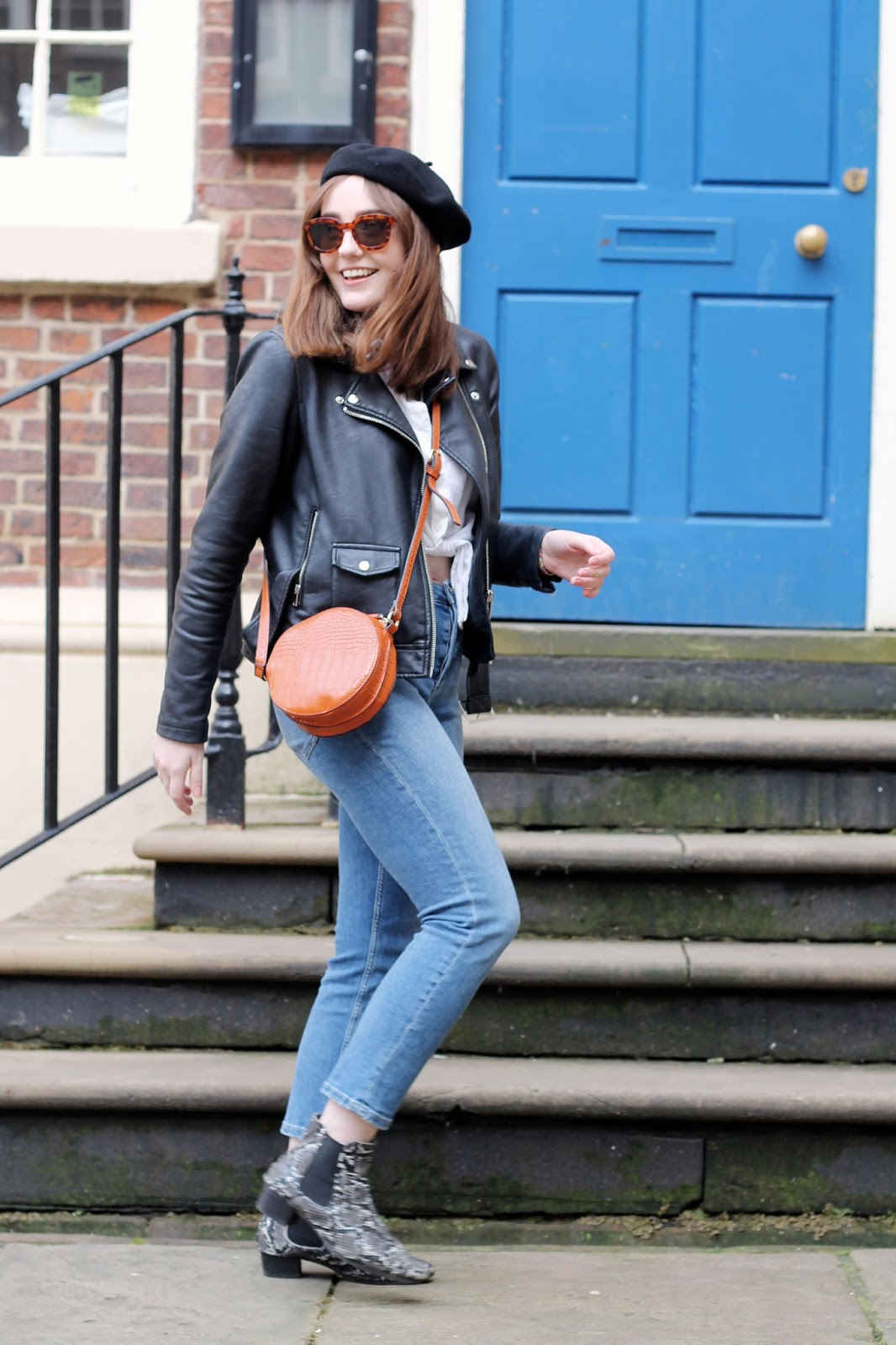 outfit style inspiration with black beret and faux leather biker jacket, white cotton shirt, blue slim leg jeans, orange circle cross body bag and snake print boots