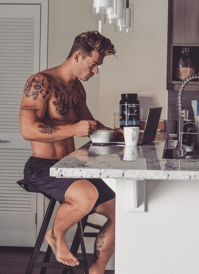 attractive-luxurious-tattoo-bare-chest-hunk-hairstyle-morning-breakfast-working-laptop