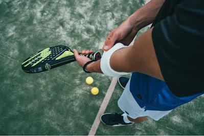 Halvkroppsbild nedre av man på padelbana som håller racket, bollar på marken.