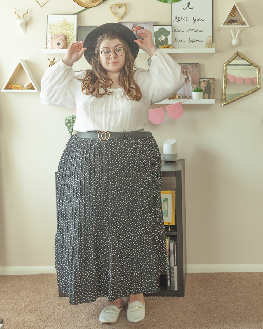 An outfit consisting of a black wide brim hat, a white square neck poet sleeved blouse tucked into a white on black microdotted pleated maxi skirt and white mules.