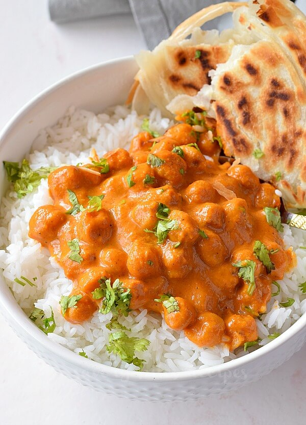 a white bowl with rice topped with chickpea tikka masala and naan