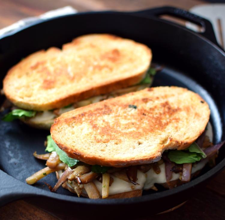 Sándwich de berenjena con pan rústico tostado sobre sartén de hierro