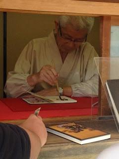 un monaco intento a compilare uno shuin