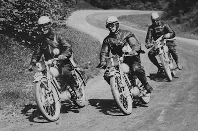 Three riders on small motorcycles lean into a corner.