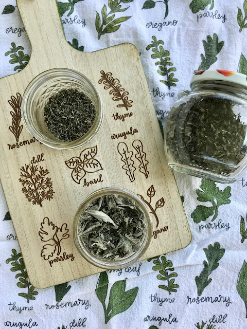 Jars of dried herbs including thyme, oregano, and sage.